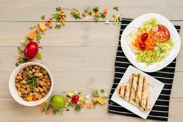 Grens gemaakt van gezond voedsel klaar maaltijd en plantaardige stukken Gratis Foto