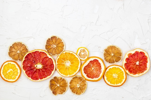 Grens van gedroogde plakjes van verschillende citrusvruchten op witte achtergrond. oranje citroengrapefruit copyspace Premium Foto