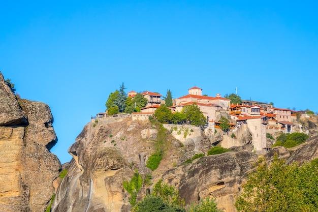 Griekenland. een heldere zomerdag in meteora. verschillende gebouwen van een rotsklooster met rode daken tegen een wolkenloze blauwe hemel Premium Foto