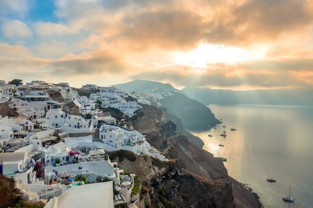 Griekenland. santorini eiland. witte huizen op het eiland santorini. jachten en catamarans in de ankerplaats. zonsopkomst Premium Foto