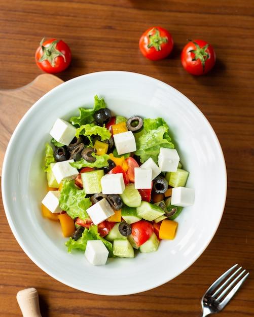 Griekse salade in de witte plaat met tomaten van boven Premium Foto