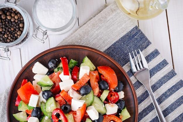 Griekse salade met tomaten, feta en olijven op een hout Premium Foto
