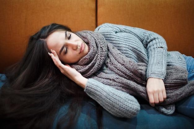Griep verkoudheid of allergiesymptoom. zieke jonge vrouw met koorts die in weefsel niest, allergieën, verkoudheid die op het bed met sjaal ligt. Premium Foto