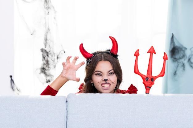 Griezelig jong meisje met duivelshoornen en drietand Gratis Foto