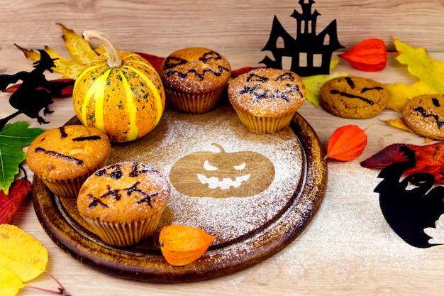 Griezelige cupcakes, pompoen, bladeren en silhouet van vleermuis op houten gerechten Premium Foto