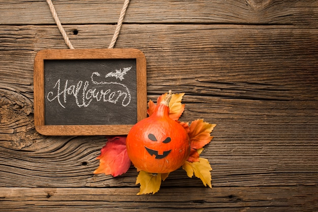 Griezelige halloween-pompoen met de herfstbladeren Gratis Foto