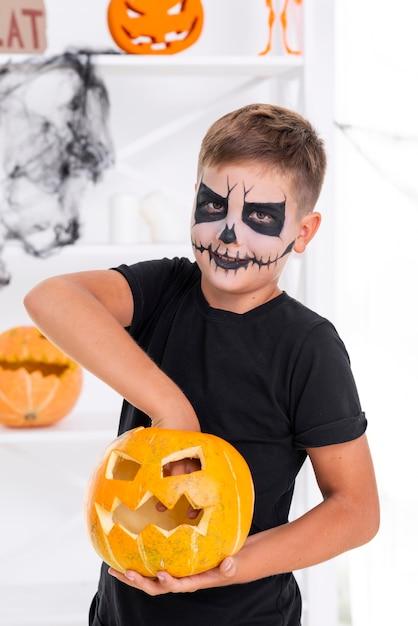 Griezelige jonge jongen met kwade halloween-pompoen Gratis Foto