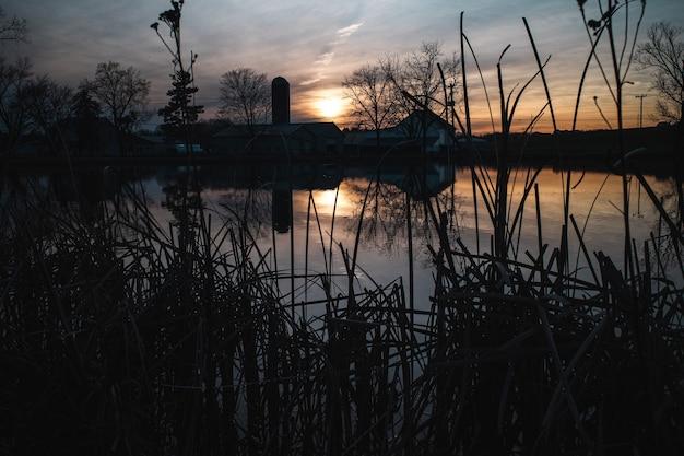 Griezelige opname van een meer met een huis eroverheen tijdens zonsondergang Gratis Foto