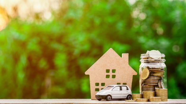 Grijs miniatuurautomodel en muntstukken op houten lijst. Premium Foto