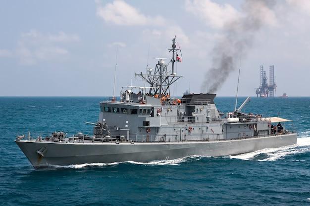 Grijs modern oorlogsschip die in het overzees varen Premium Foto