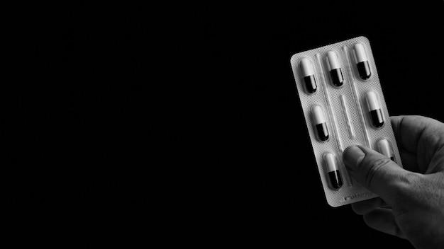 Grijsschaal die van een persoon is ontsproten die een pak capsules met een zwarte houdt Gratis Foto
