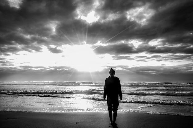 Grijsschaal die van een vrouw is ontsproten die op het strand met het zonlicht in de bewolkte hemel staat Gratis Foto