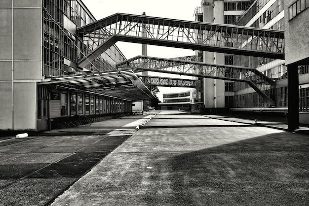 Grijsschaal opname van bruggen met glazen ramen die twee gebouwen met elkaar verbinden Gratis Foto