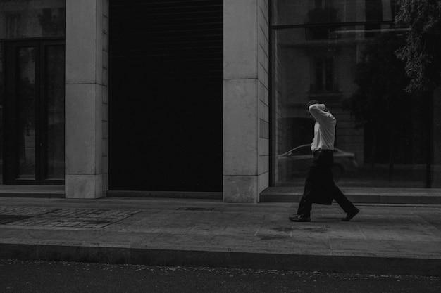 Grijsschaal shot van een man lopen langs een voetgangersgebied in de buurt van een gebouw Gratis Foto