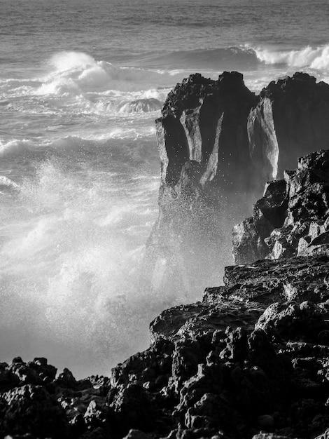 Grijstinten die van sterke golven grote rotsen op een kust raken met waterspatten en nevel Gratis Foto