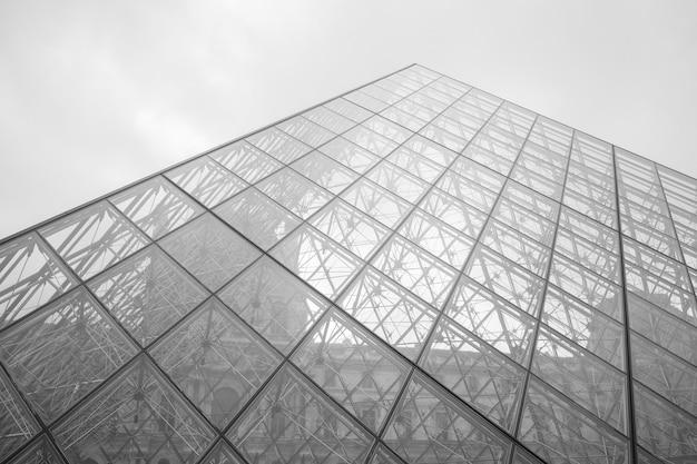 Grijstinten shot van het louvremuseum onder een bewolkte hemel in parijs, frankrijk Gratis Foto