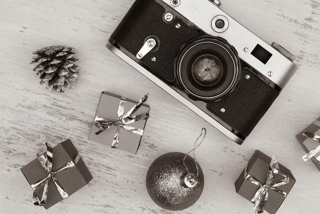 Grijstinten shot van kerst geschenkdozen en camera Gratis Foto