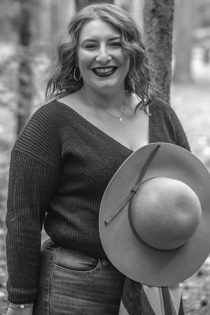 Grijstinten van een glimlachende vrouw met een hoed in een bos Gratis Foto