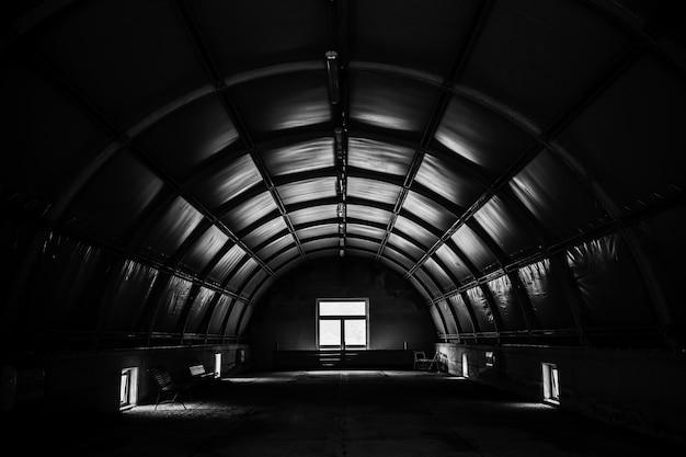 Grijstintenopname van een donkere tunnelkamer met een raam Gratis Foto