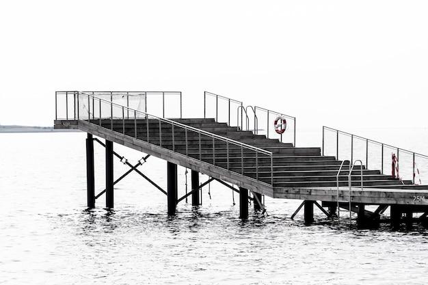 Grijstintenopname van een trap naar een plek om boven de zee te staan Gratis Foto