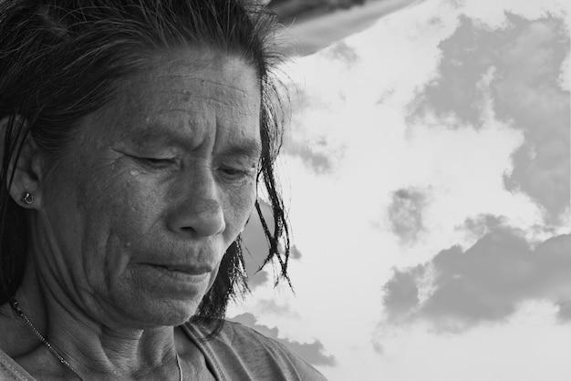 Grijswaardenfoto van oudere vrouw die voedsel bereidt onder een buitenluifel in de filippijnen Gratis Foto