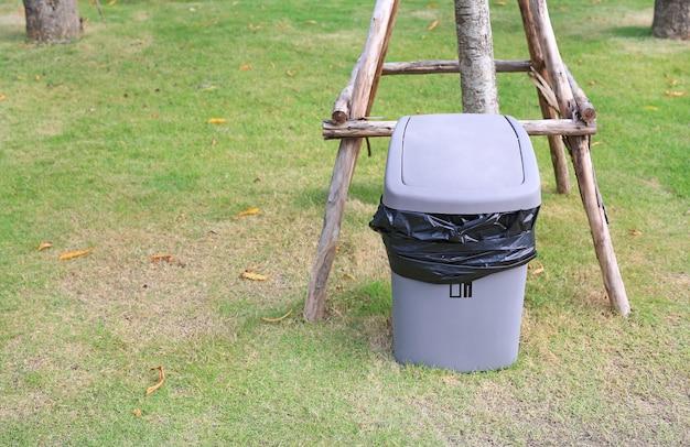 Grijze bak voor algemeen afval in openbare tuin Premium Foto
