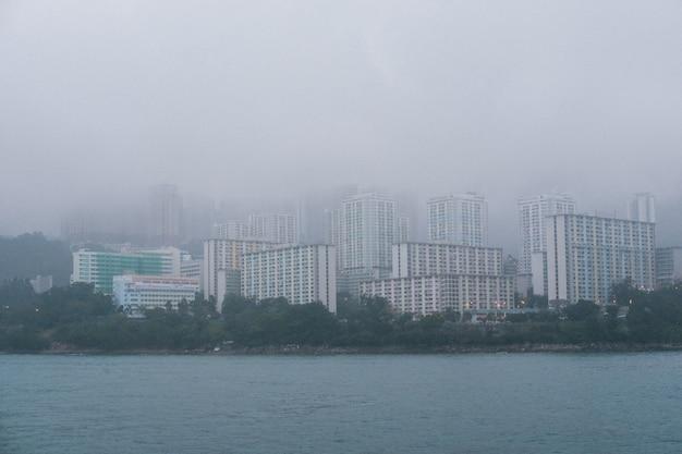 Grijze betonnen hoge wolkenkrabbers aan de kust bij mistig weer Gratis Foto