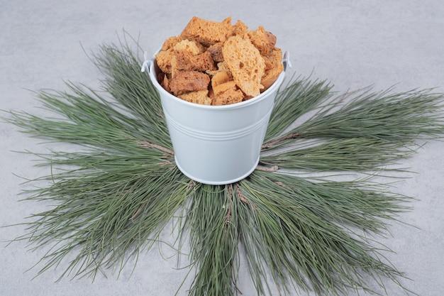 Grijze emmer vol crackers op groene tak van de boom. hoge kwaliteit foto Gratis Foto