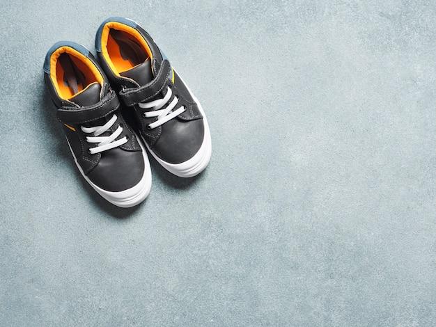 Grijze en gele sneakers op grijs Premium Foto