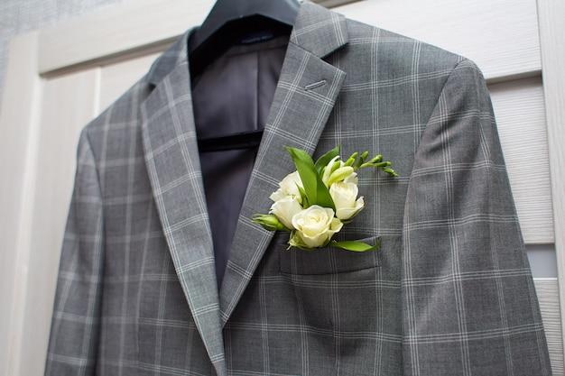 Grijze jas in een kooi met een corsage aan de deur Premium Foto