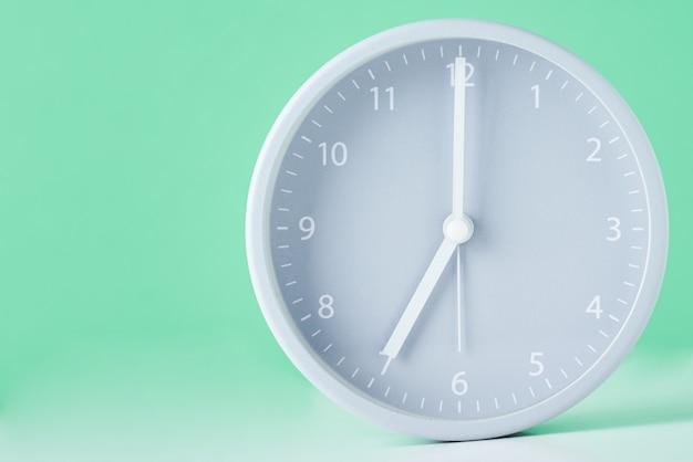 Grijze klassieke wekker op een pastel groen met kopie ruimte Premium Foto