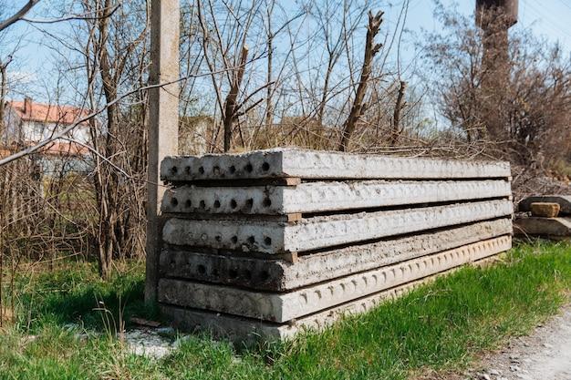 Grijze, oude betonplaten die op een bouwplaats op elkaar zijn gestapeld. Premium Foto