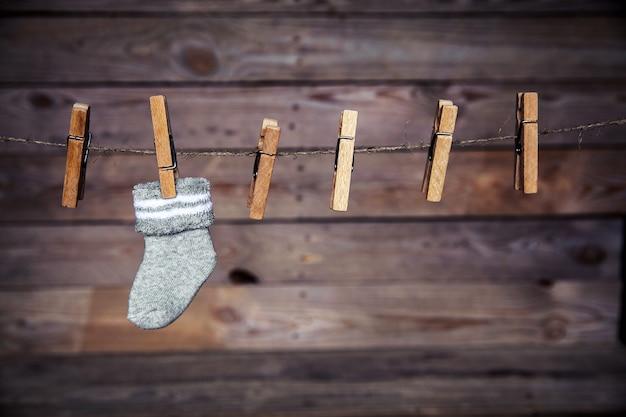 Grijze sok met een wasknijper op een houten muur Premium Foto
