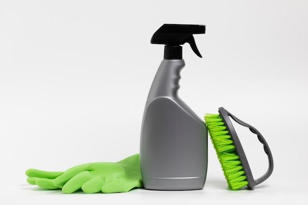 Grijze spuitfles met groene handschoenen en borstel Gratis Foto