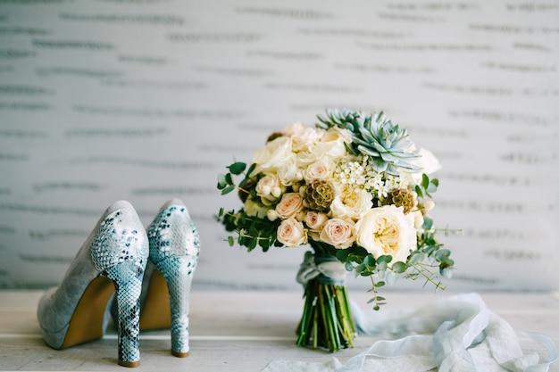 Grijze suède schoenen met hakken van slangenleer naast een bruidsboeket met zijden linten Premium Foto