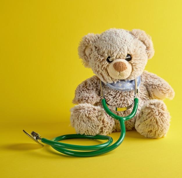 Grijze teddybeer en groene medische stethoscoop op een geel Premium Foto