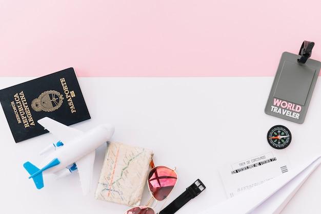 Grijze wereldreizigerslabel met paspoort; kaart; kompas; kaartjes; speelgoedvliegtuig; zonnebril en polshorloge op dubbele achtergrond Gratis Foto
