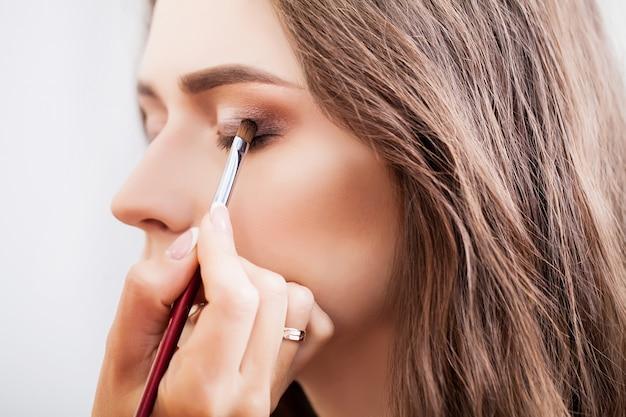 Grimeur die make-upmeisje in de salon doen, schoonheidsconcept Premium Foto