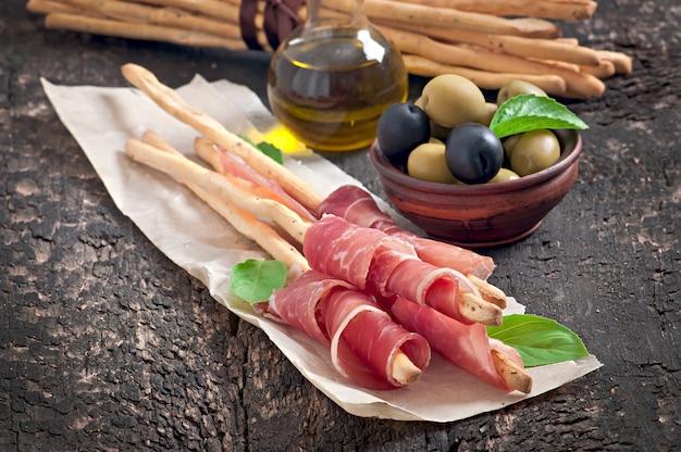 Grissini-broodstokken met ham, olijven, basilicum op oud hout Gratis Foto