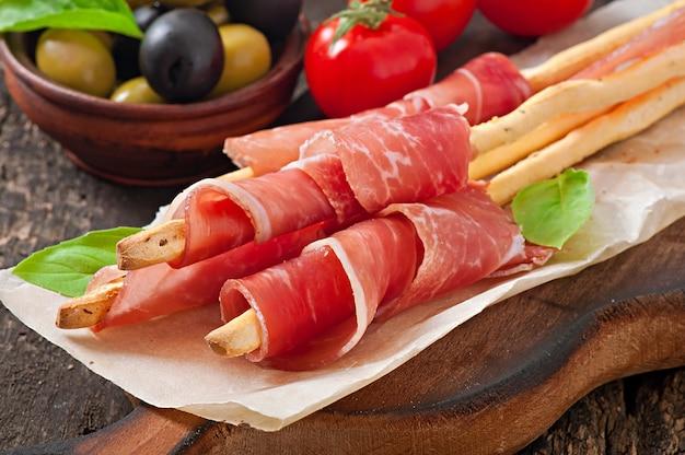 Grissini-broodstokken met ham, olijven, basilicum op oude houten Gratis Foto