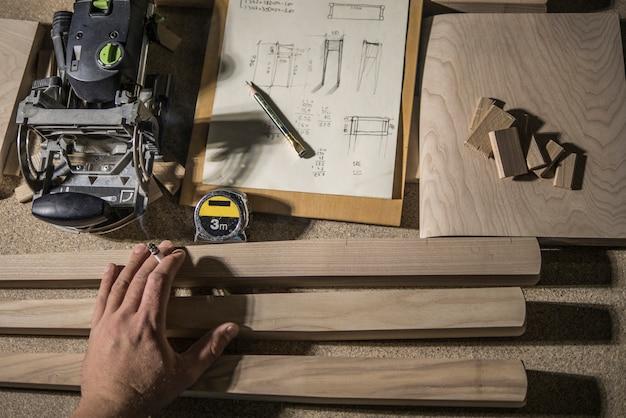 Groefmolen, potlood en meetlint, houten spaties en meubelmakerhand met een sigaret Premium Foto