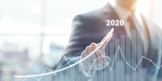Groeisucces in 2020 concept. zakenmanplan en verhoging van positieve indicatoren in zijn zaken. Premium Foto