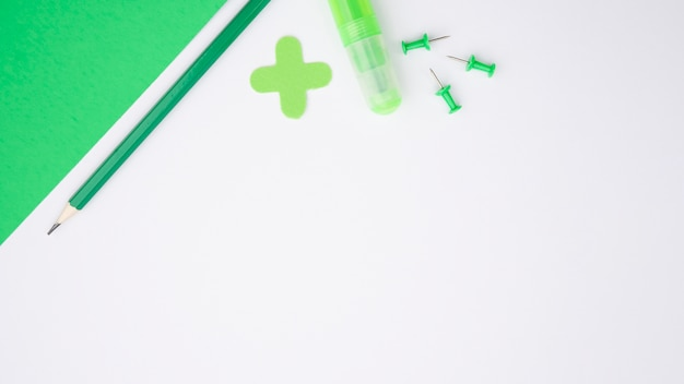 Groen ambachtelijk papier; potlood; lijm en duw de pen over het witte oppervlak Gratis Foto