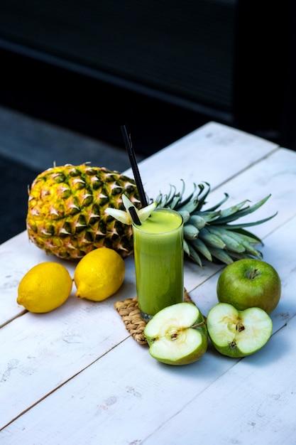 Groen appelsap dat met appel, ananas en citroenen op witte houten lijst wordt gediend Gratis Foto