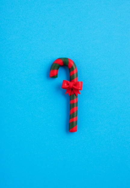 Groen en rood suikergoedriet met een boog op de blauwe achtergrond, kerstsfeer Gratis Foto