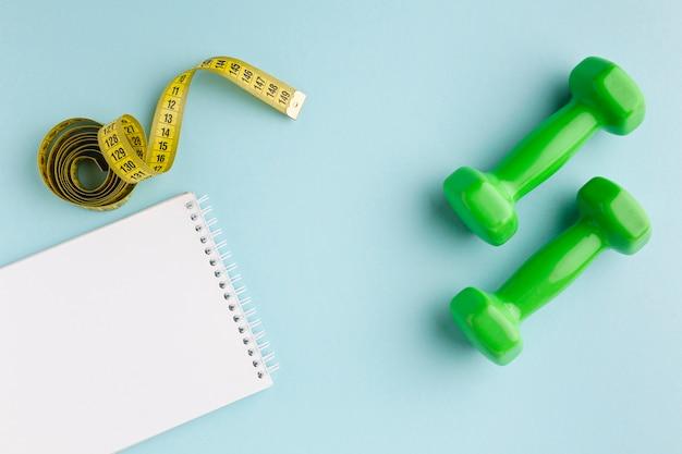 Groen gewichten en notitieboekje op blauwe achtergrond Gratis Foto