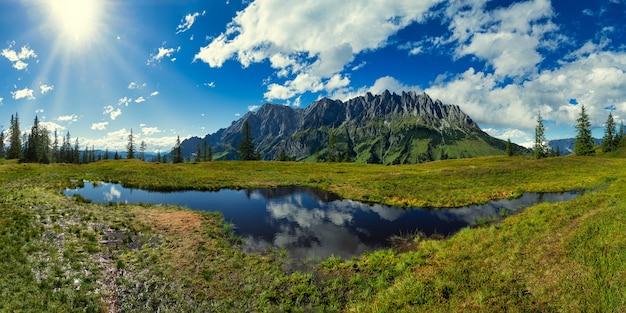 Groen grasveld in de buurt van meer onder blauwe lucht en witte wolken overdag Gratis Foto