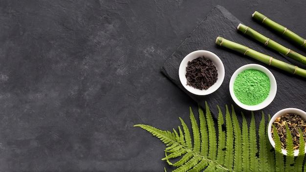 Groen matcha theepoeder en droog kruid met bamboestok op zwart gestructureerd oppervlak Gratis Foto