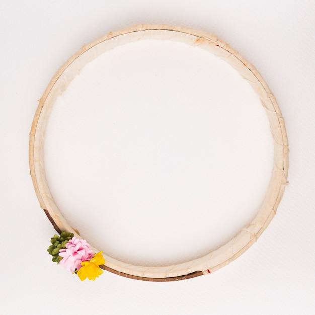 Groen; roze en gele bloemen op houten circulaire frame tegen een witte achtergrond Gratis Foto