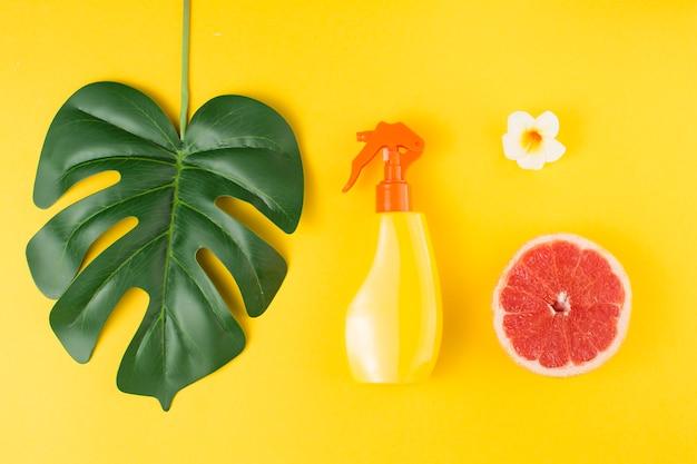 Groen tropisch installatieblad dichtbij nevelfles en fruit Gratis Foto